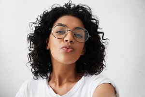 Young attractive African woman posing with kiss on her lips, wearing trendy spectacles, having flirty look feeling confident and beautiful. Charming dark-skinned girl with Afro hair having fun indoors