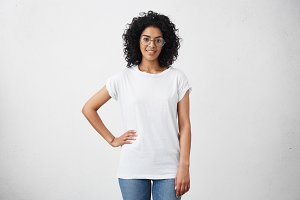 Stylish young dark-skinned female with curly hair looking at camera and smiling cutely, posing with hand on her waist, isolated on white background with copy space for your promotional content