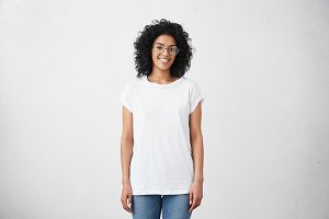 Happy young woman standing at blank white studio wall, participating in social media advertisement, saying couple words about her experience being student at camera, looking positive and joyful