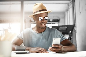 Relaxed carefree young bearded Afro American man in stylish eyewear and hat sitting alone at cafe table, using smart phone, reading text message with joyful smile while having cappuccino during lunch