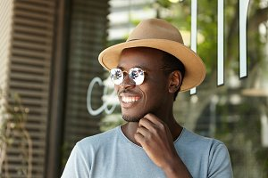 Happy dark-skinned European male youngster in hat and sunglasses relaxing at sidewalk cafe on sunny summer day, waiting for his lunch, smiling cheerfully, enjoying nice weather and leisure time