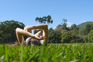 Young woman lying on green grass in park and relaxing. Girl sitting on meadow at nature and watching at the sky. Female looking at the landscape and enjoying vacation. Low angle of view Rear Back view