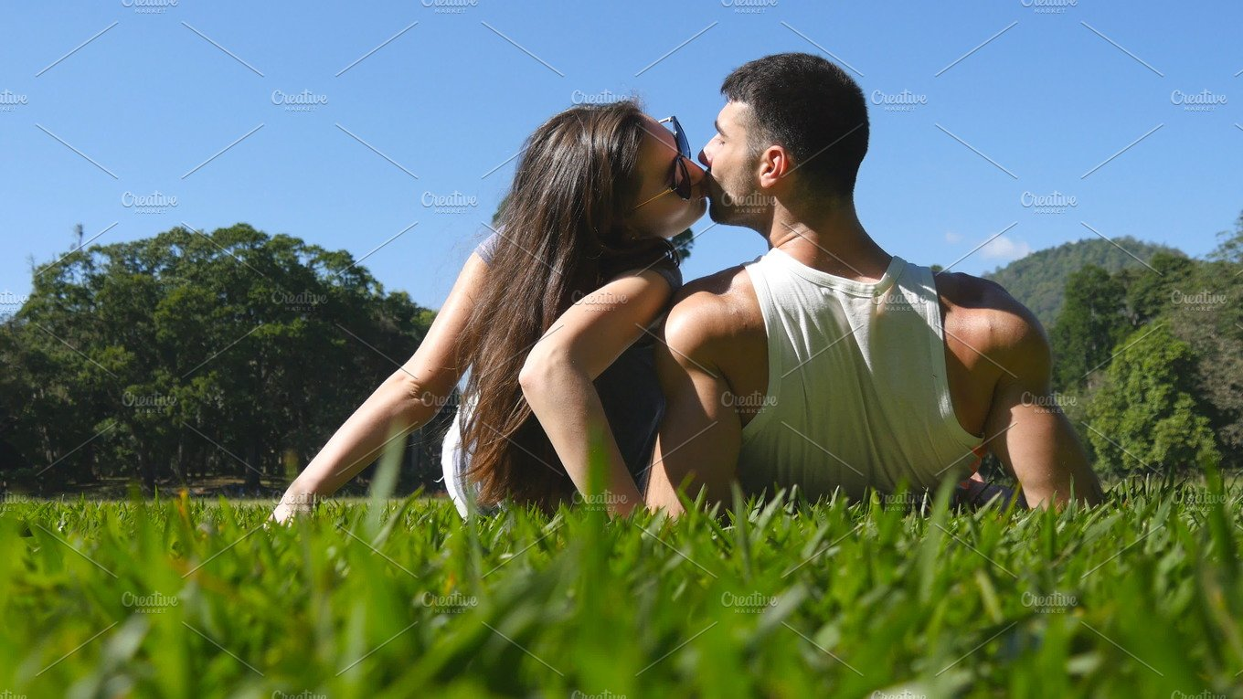 Young Couple Lying On Green Grass In Park And Relaxing