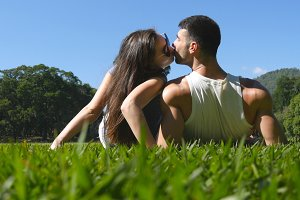 Young couple lying on green grass in park and relaxing. Man and woman sitting on meadow at nature and kissing. Girl and boy looking at the landscape and enjoying vacation. Rear Back Low angle of view