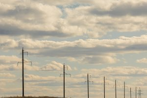 Row of electricity pylons and lines at summer field, sunny day