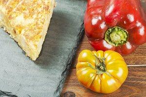 Potato omelette, a pepper and a tomato. Spanish
