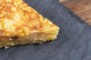 Small portion of potato omelette on a slate plate. Spanish typical food.