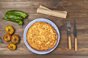 Omelette served with vegetables on wooden table. Cookware.