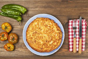 Omeletteserved with vegetables on wooden table. Horizontal shoot.