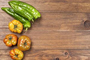Tomatoes and peppers on wooden table.