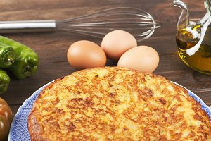 From above plate with typical Spanish omelette, cookware and fresh vegetables on wooden table.