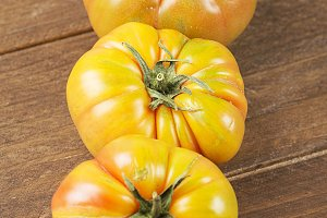 Appetizing tomatoes on wooden table