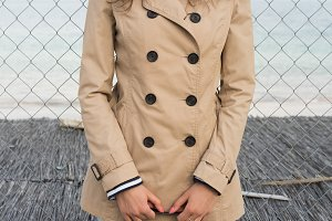 Girl in a beige coat on the coast
