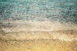 Sandy beach and transparent sea waves, pebbles under the water