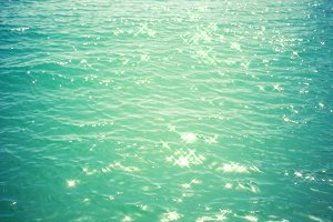 Sea background - turquoise water with glare of light