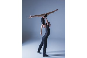 two young modern ballet dancers on blue studio background