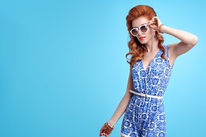 Fashion redhead Model in Summer Jumpsuit on Blue