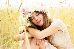 Natural beauty. Portrait of beautiful young girl dressed in white dress and flowers on her head is sitting in yellow wheat field.