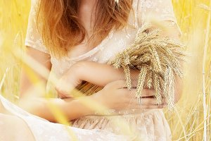 Nature portrait. Closeup of beautiful woman in white dress is keeping wheat cropin her hands while sitting in yellow wheat field.