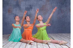Three young ballerinas posing on the floor