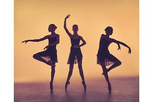 The silhouettes of young ballet dancers posing on a gray backgro