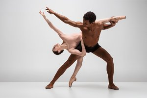 Couple of ballet dancers posing over gray background