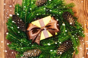Wreath on the wooden board. Wrapped gift box. Christmas and New year concept