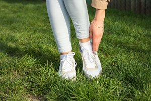 Legs in jeans and white sneakers
