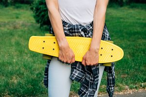 Girl holding a yellow skateboard