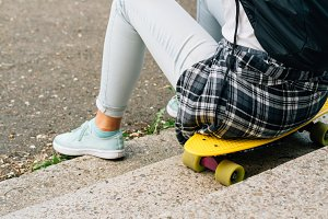 Girl sitting on yellow skateboard