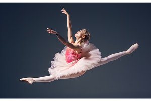 Beautiful female ballet dancer on a grey background. Ballerina is wearing  pink tutu and pointe shoes.