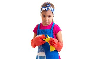 Girl in apron and gloves holding spray and duster