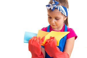 Girl in apron and gloves holding dusters