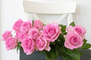 Pink roses in wooden box and chair