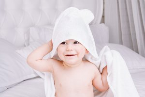 Adorably baby lie on white towel in bed. Happy childhood and healthcare concept.