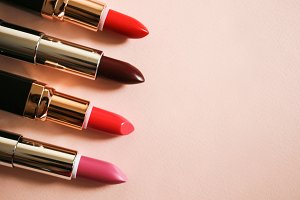 Set open lipsticks on a beige background