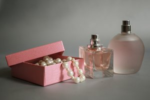 Perfume bottles and pink box with pearl beads on a gray background