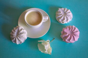 Pink and white marshmallows and cup with a cappuccino on a turquoise background