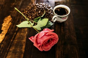 Coffee beans, cup and rose