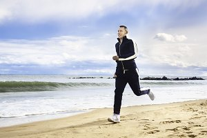 Adult man running on ocean beach
