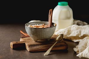 Traditional rice pudding with cinnamon. Dark background. Tasty and nutritious breakfast.