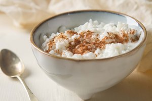Traditional rice pudding with cinnamon. Light background. Tasty and nutritious breakfast.