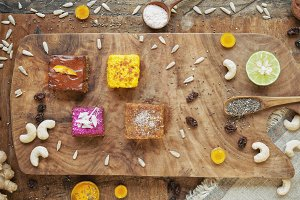 Four pieces of different raw cakes on wooden board