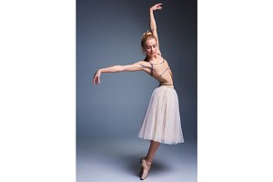 Young beautiful ballerina dancer dancing on a studio background