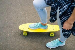 Female legs on yellow skateboard