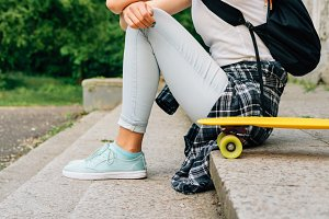 Girl sitting near her skate