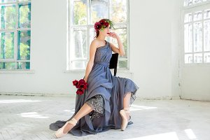 The beautiful ballerina sirtting in long gray dress