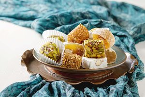 Eastern sweets. Turkish delight with pistachios in a vase. The fabric on  white background