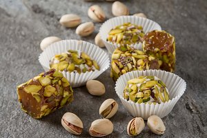 Eastern sweets. Turkish delight with pistachios in a vase. Dark gray stone background.