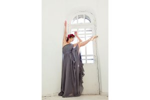 The beautiful ballerina posing in long gray dress